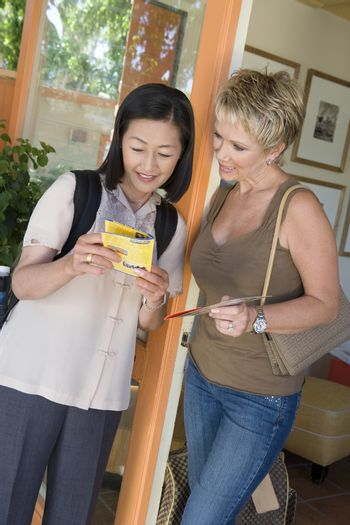 Happy female friends reading pamphlet of the resort