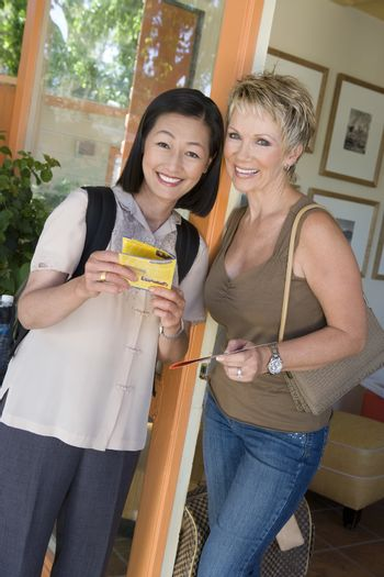 Portrait of happy female friends with pamphlet at resort