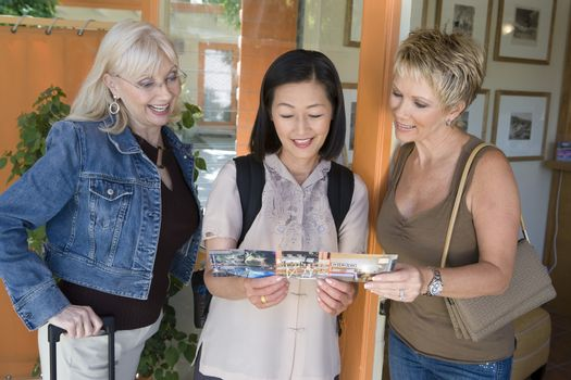 Three female friends reading pamphlet of the resort