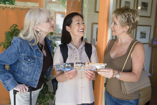Three female friends communicating while holding pamphlet of resort