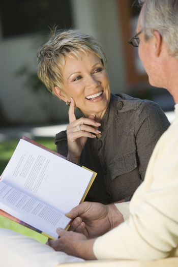 Mature couple looking at each other with man holding novel