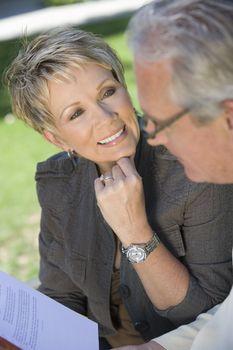 Happy mature woman looking at man reading novel