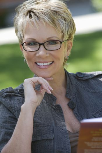 Portrait of a happy mature woman in glasses with novel