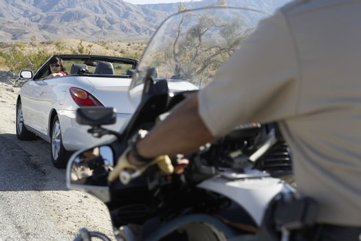 Cropped police officer on a motorbike stopping car on the desert road