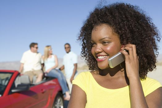An African American happy woman on a call with friends in the background