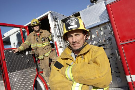 Portrait of a confident firefighter with coworker in the background