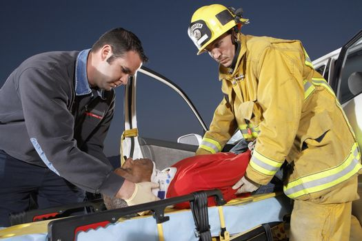 Fire fighter and paramedic assisting man at crash site