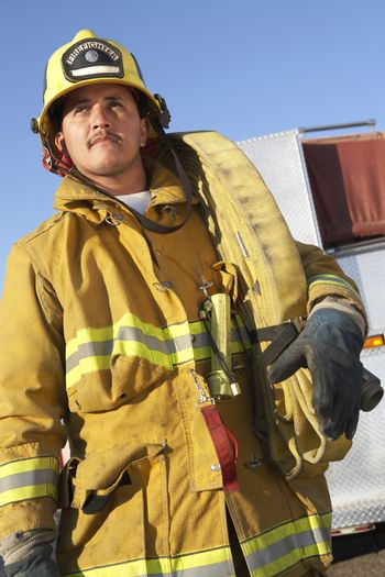 Mature adult fire worker carrying firehose on shoulder