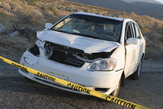 Damaged car behind warning tape at an accident scene