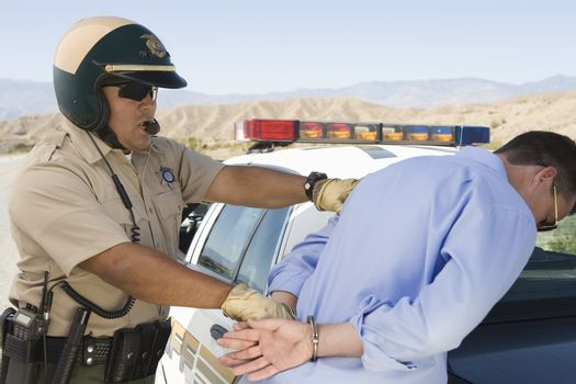 Mature traffic officer arresting man for breaking traffic rules