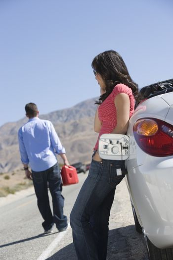 Woman on call by car while man with gasoline can in the background on desert roadside