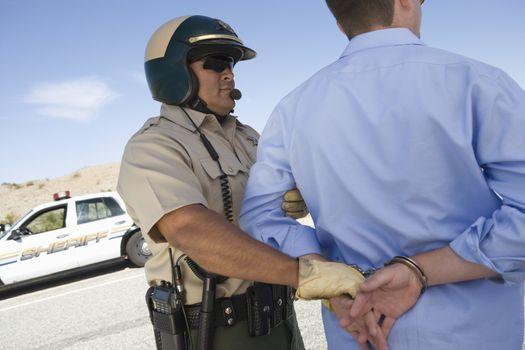 Mature traffic cop arresting man for breaking traffic rules
