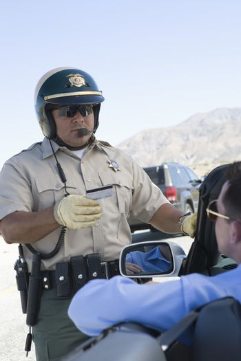Mature traffic officer checking license