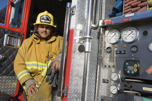 Portrait of a mature fire fighter sitting at fire brigade's door