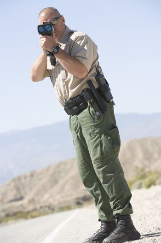 Full length of a mature traffic officer monitoring speed through radar gun