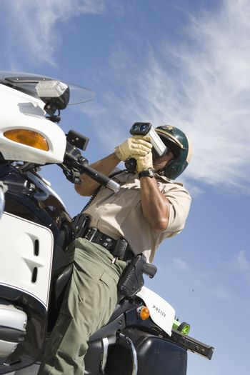 Low angle view of a mature traffic officer sitting on bike and monitoring speed through radar gun