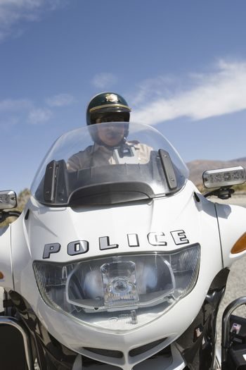 Mature police officer riding motorbike