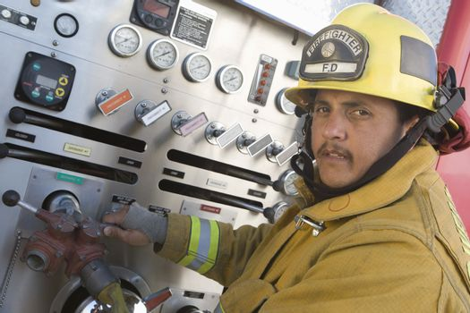 Portrait of a mature fire fighter turning on water gauge