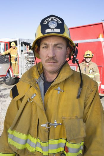 Portrait of a mature fire worker with coworkers in the background