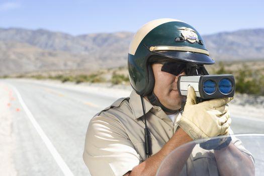 Mature traffic officer monitoring speed through radar gun