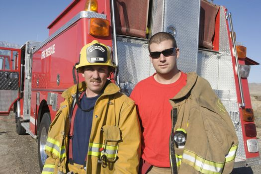 Portrait of happy fire workers standing with fire brigade in the background