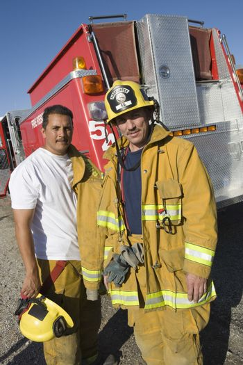 Portrait of confident fire workers standing with fire brigade in the background
