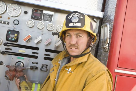 Portrait of a mature fire worker holding fire hose