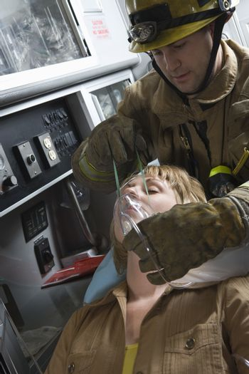 Firefighter helping an injured woman in ambulance