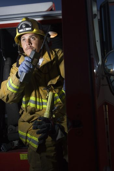 Fire fighter having conversation on walkie talkie