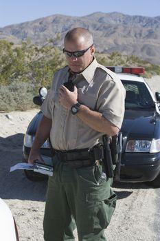 Mature traffic officer holding walkie talkie