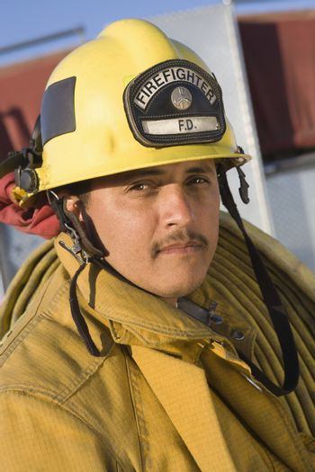 Portrait of a mature fire fighter carrying fire hose on shoulder