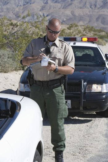 Mature traffic officer in uniform writing ticket