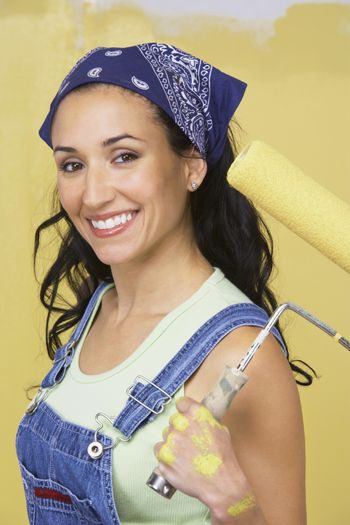 Portrait of happy woman in overalls holding roller paint