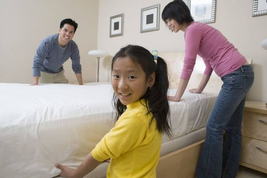 Family Preparing Bed Together