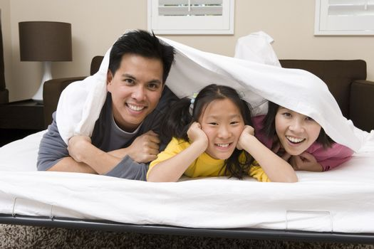 Portrait of a happy family hiding under the blanket in bedroom