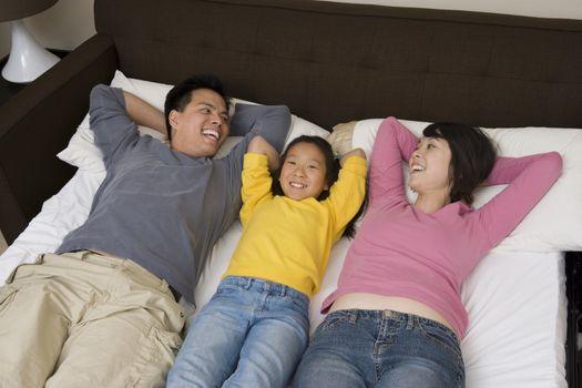 Portrait of a happy girl lying between her parents in bed