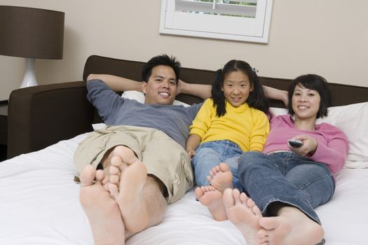 Portrait of happy family with daughter watching television in bed