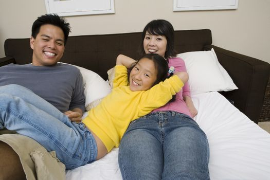Portrait of a happy family with daughter relaxing in bed