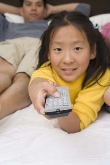 Portrait of a teenage girl watching television with father in bed