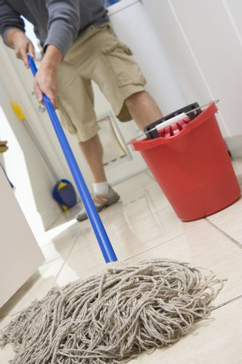 Low section of a man mopping on the floor