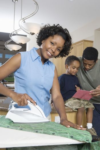 Portrait of woman ironing clothes with man assisting child in homework