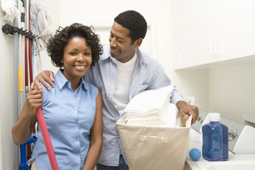 Portrait of a woman with man doing household chores