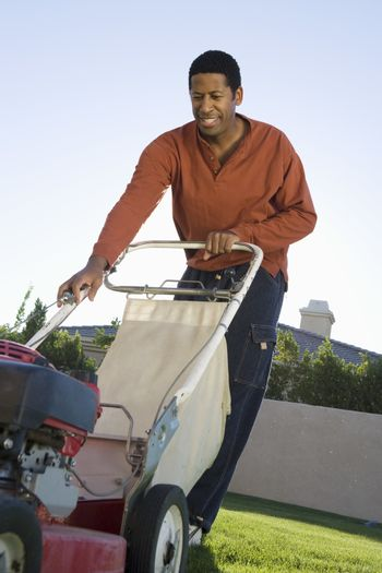 Middle aged African American man holding a lawn mower in the lawn