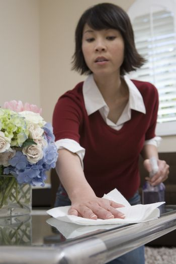 Mature woman whisking with napkin on table