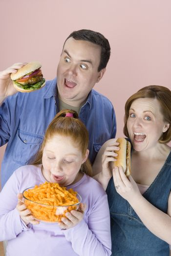Obese family eating junk food isolated over pink background