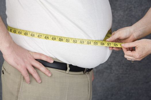 Mid section of hands measuring abdomen of obese man over colored background