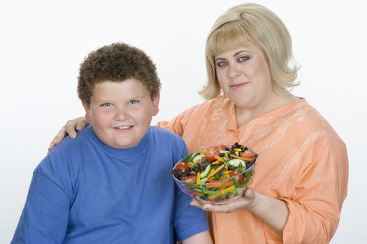 Portrait of mother and son holding bowl of salad isolated over white background
