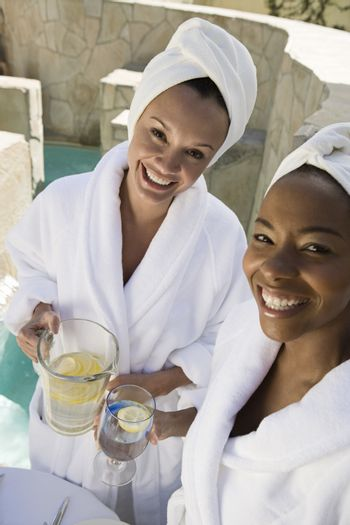 Portrait of female friends in bathrobe holding pitcher and glass
