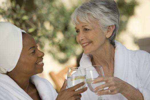 Happy women in bathrobe toasting drinks