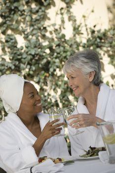 Women in bathrobe toasting drinks